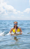 A young girl wearing yellow swimsuit swims Royalty Free Stock Photos
