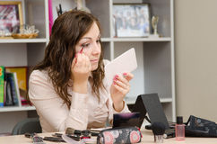 Young girl wears a brush lashes at desk in office Stock Image