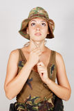 A young girl wears a camouflage hat. Gray background. Royalty Free Stock Images