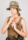A young girl wears a camouflage hat. Gray background. Royalty Free Stock Photos