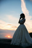 Young girl in wedding dress in park posing for photographer. Sunny weather, summer. Royalty Free Stock Images