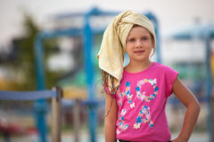 Young girl with wet hair, aqua park in the background blured. Summer fun at aqua park Royalty Free Stock Photo