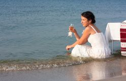 Young girl in a wet white dress sitting with a glass of champagne in his hand by the sea Royalty Free Stock Photos
