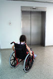 Young girl on wheelchair. Waiting for the lift (elevator Stock Image