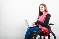 Young girl on wheelchair surfing web. Stock Image