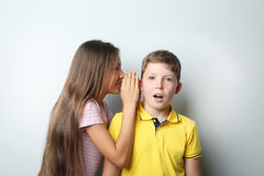 Young girl whispering a secret to boy. On grey background Stock Photos