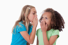 Young girl whispering a secret to her friend Royalty Free Stock Photography