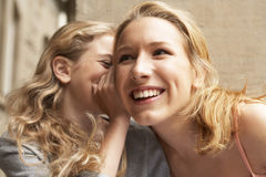 A young girl whispering something into another girls ear. Royalty Free Stock Images