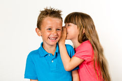 Young girl whispering to young boy Stock Images