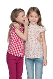 Young girl whispers to her friend Royalty Free Stock Photography