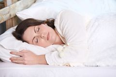 Young girl. White bed. Healthy sleep. Brown hair. Light skin Royalty Free Stock Photography