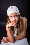 Young girl with white cap on black background Royalty Free Stock Photo