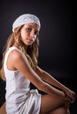 Young girl with white cap and sober look sitting on black backgr Stock Photo