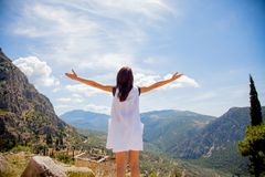 Young girl in white clothes standing on rock in Greece. With view at mountains royalty free stock image