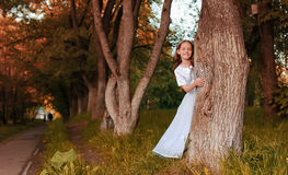 Young girl in a white dress against a tree in autumn Royalty Free Stock Image