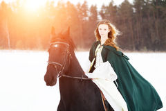 Young girl in white dress and cape riding horse Royalty Free Stock Images
