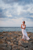 The young girl in a white dress costs on a stone pier against th Royalty Free Stock Photos