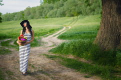 Young girl in white dress and hat holding basket of roses stock photo