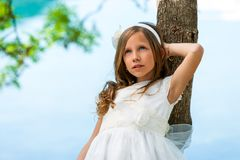 Young girl in white dress resting against tree. Royalty Free Stock Image