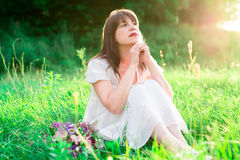 Young girl in white dress sitting in the middle of the field and reflects. Sadness, loneliness, doubt. Stock Photo