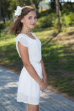 Young girl in white dress standing. With a flower in her hairs Stock Photo