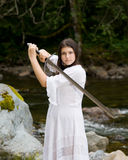 Young girl in white dress with two handed sword Royalty Free Stock Images