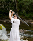 Young girl in white dress with two handed sword Royalty Free Stock Photo