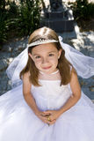 Young girl in white dress and veil outdoors Stock Photo
