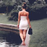 Young girl in a white dress walk coast of the river Royalty Free Stock Images