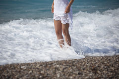 Young girl in white dress walking on the sandy tropical beach Royalty Free Stock Photos