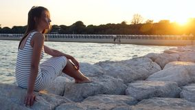 Young girl in white frock sits on rocks on the stone beach at the sea in sunset. Lonely woman sitting on big rocks, smiling laughing and looking to the camera stock video
