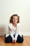 Young girl with white fur vest. Portrait young girl with white fur vest sitting on wood floor Royalty Free Stock Image