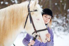 Young girl with white horse in winter forest Royalty Free Stock Images