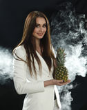 A young girl in a white jacket holds a pineapple in her hands and smiles on a black background, covered with smoke vapor Stock Images