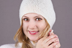 Young girl in a white knitted cap on the grey b. Portrait of a young beautiful girl in a white knitted cap on the grey background Stock Photo