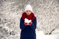Young girl in white knitted hat, red scarf and mittens blows snow Royalty Free Stock Photo