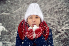 Young girl in white knitted hat, red scarf and mittens blows snow Stock Photo