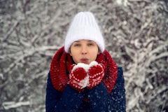 Young girl in white knitted hat, red scarf and mittens blows snow Stock Photography