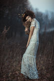 Young girl in a white lace dress, a crown of twigs with a bouque Royalty Free Stock Image