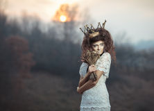 Young girl in a white lace dress, a crown of twigs with a bouque Royalty Free Stock Photography