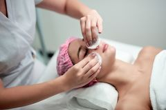 Young girl in white medical coach in cosmetological salon getting her face cleaned by proffecional cosmetologyst stock images