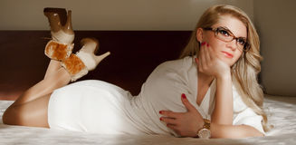 Young girl with with white mini skirt  lying on the bed Royalty Free Stock Photos