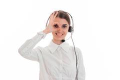Young girl in white shirt and headphones with microphone smiling keeps your hand near your eyes and looking at camera Royalty Free Stock Images
