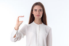 Young girl in white shirt reveals one hand with fingers clasped isolated on  background Stock Photo