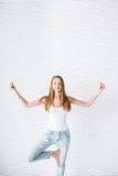 Young girl in white singlet and blue denim with holes makes meditation on yoga exercise Stock Images