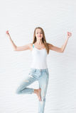 Young girl in white singlet and blue denim with holes makes meditation on yoga exercise Royalty Free Stock Photography