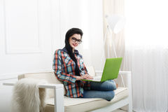 Young girl on white sofa with a laptop. Stock Photos