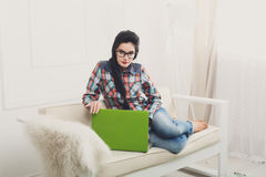 Young girl on white sofa with a laptop. Royalty Free Stock Photos