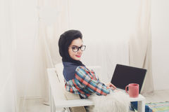 Young girl on white sofa with a laptop. Stock Photo