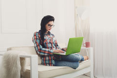 Young girl on white sofa with a laptop. Royalty Free Stock Image